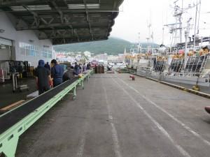 入港の連絡を受け、関係者が荷揚げの準備をする様子